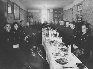 Frankwell air raid wardens having a celebratory dinner at the Cross Guns pub, which used to stand on the corner of New Street and Chapel Street, Frankwell. Demolished in the 1960s. This picture believed to be wartime. At the head of the table in the distance was the man in charge, chief warden Jimmy McNamara, a local butcher and later mayor. Fourth in from the front, right, is Eric Reece, looking at the camera. He was a butcher too. Front, either side, are Mr and Mrs Jones, who were married and lived on the corner of New Street and Dummy Lane. Just beyond Eric Reece is Bert Chant (face partly obscured) who was on the Great Western Railway. Picture via Shrewsbury historian David Trumper. ARP dinner. Library code: Shrewsbury nostalgia 2004. Frankwell nostalgia 2004.