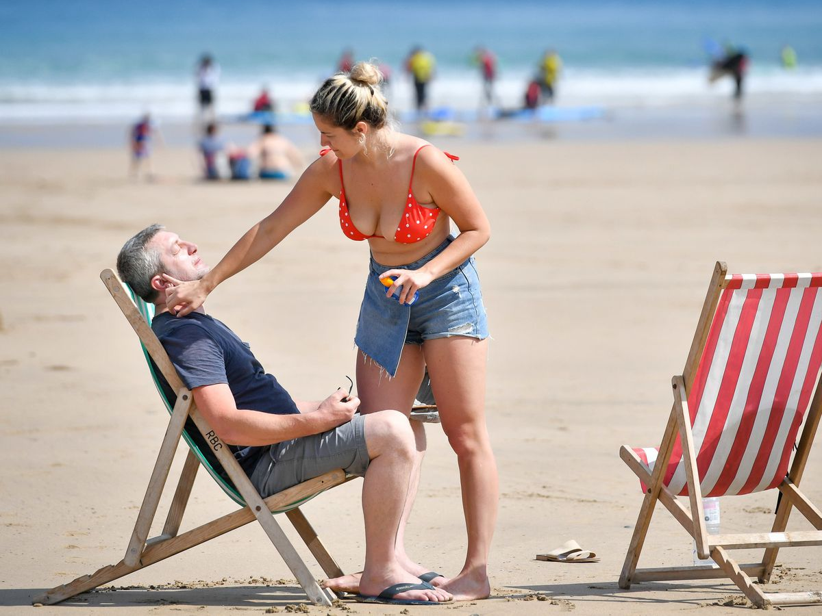 People apply sunscreen on the beach in Newquay, Cornwall