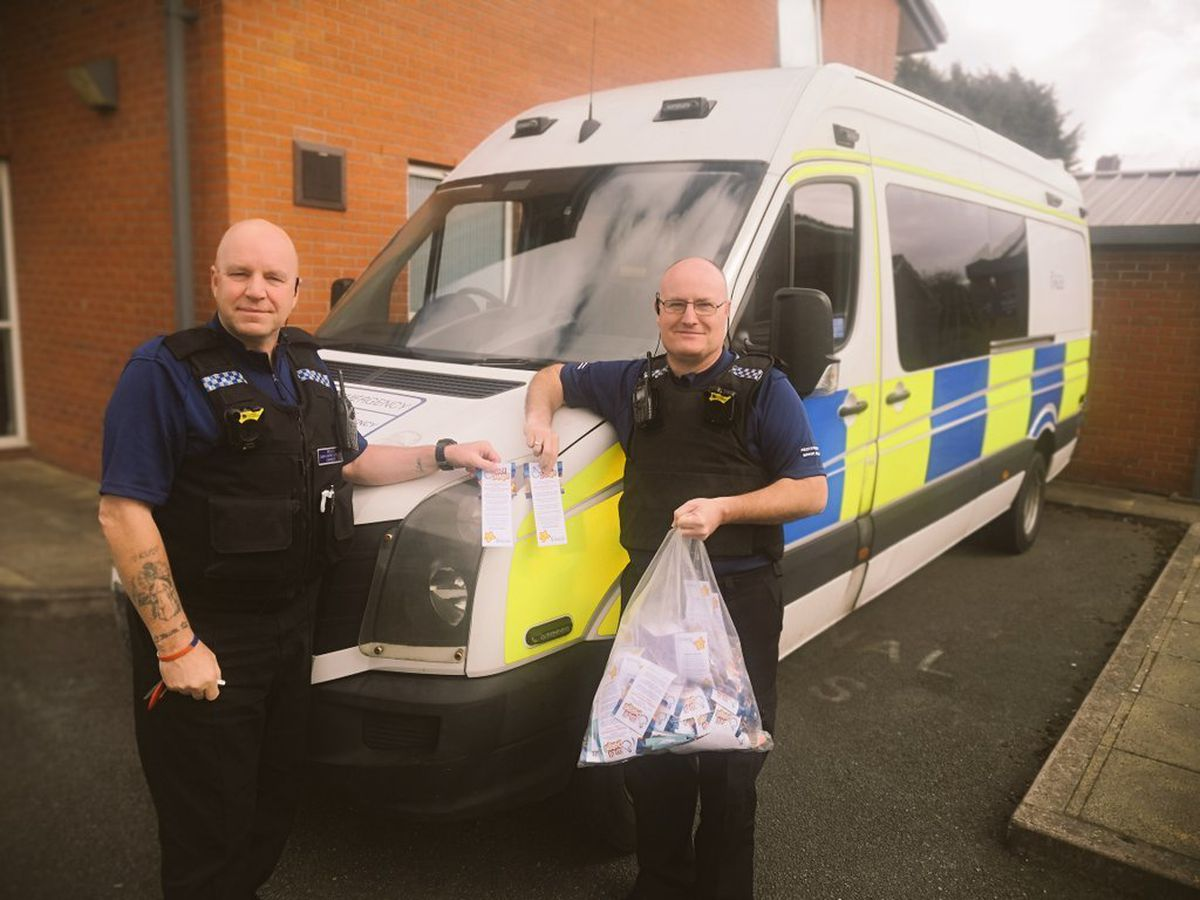 PCSOs Liston and Protheroe with bags of sweets and notes for children
