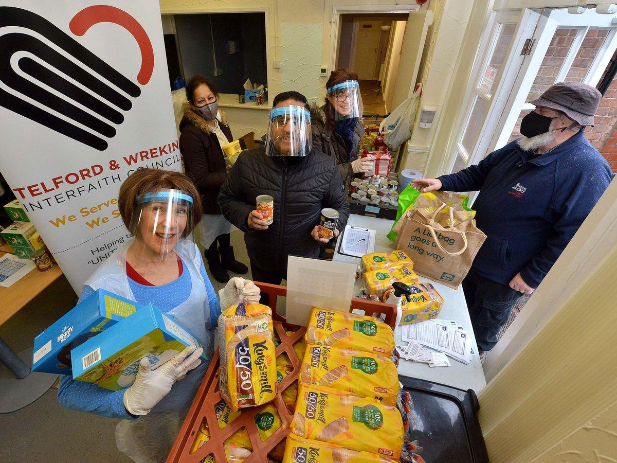 Members of Interfaith Telford & Wrekin, including chairman Raj Mehta, hand out breakfast parcels