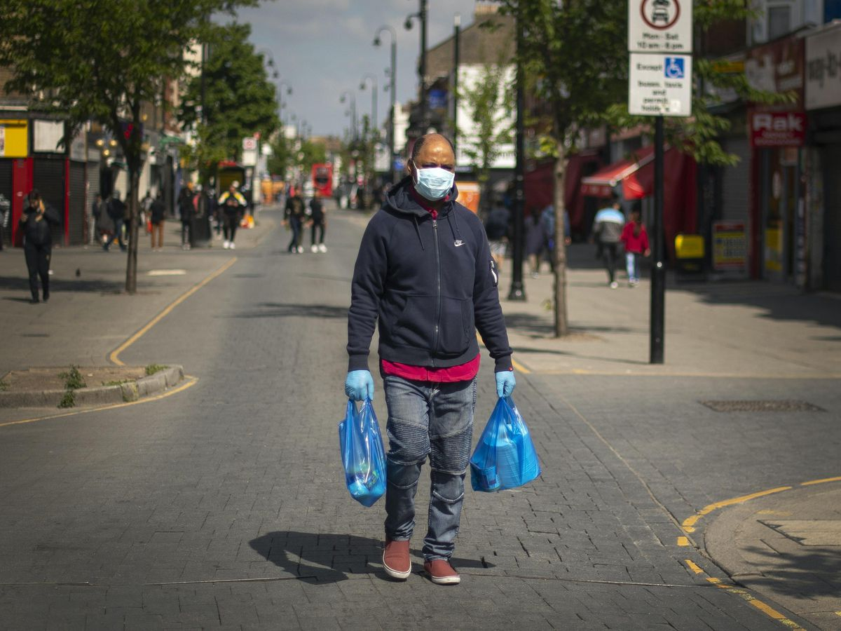A man carries bags of shopping
