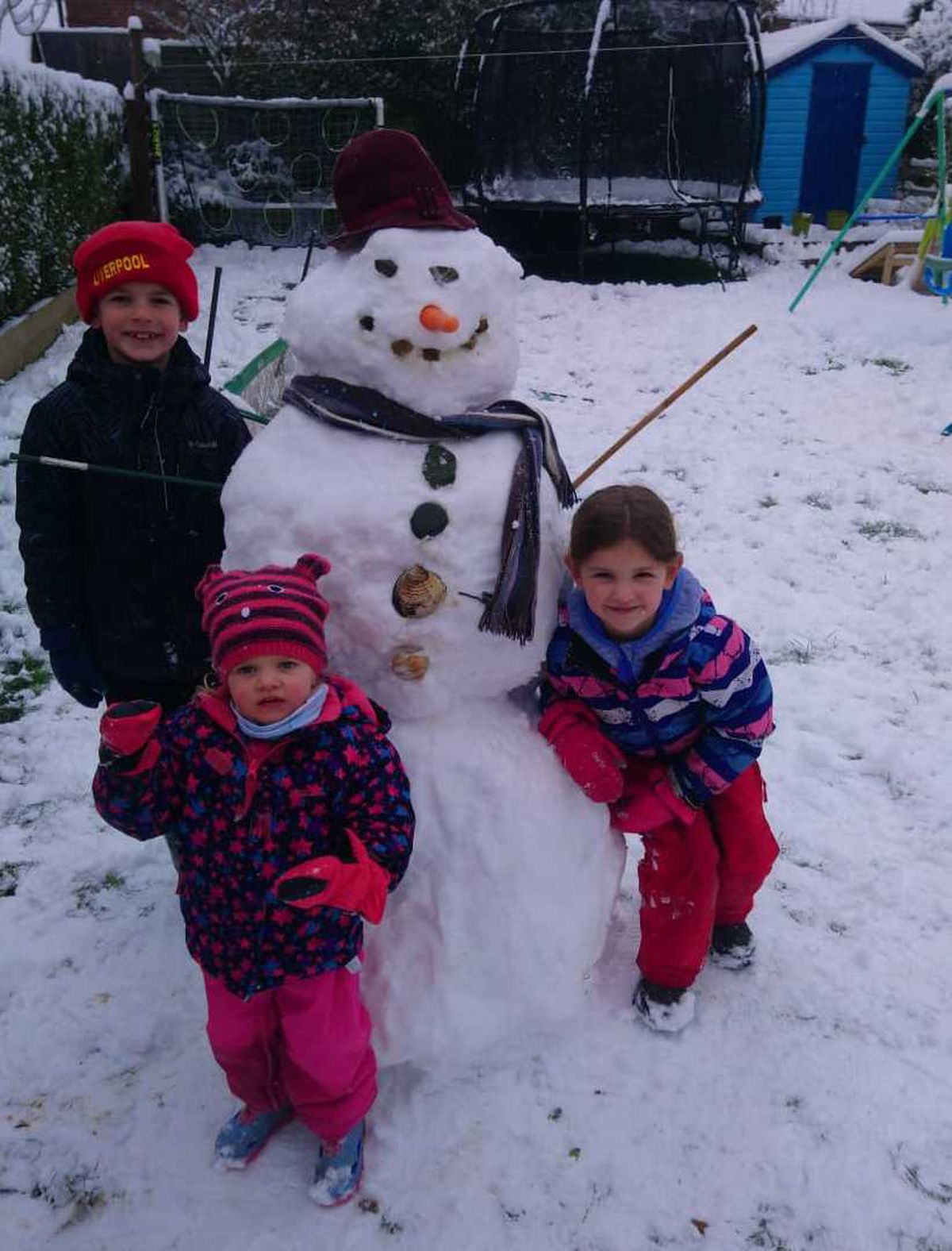 Charlie, Poppy and Emily Roberts with their snowman in Oswestry