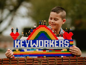 Hayden Bolton, aged 10 and from Shrewsbury, with the Lego rainbow he and his step-father made for key workers