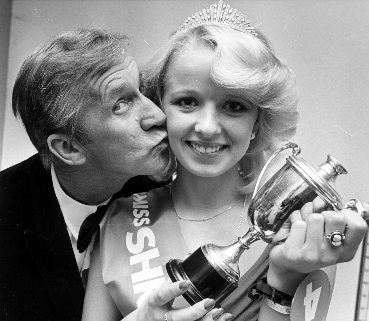 As we don't publish tomorrow, Valentine's Day, we'll bring you a kiss today. Here the 1981 Miss Shropshire, 21-year-old Lyn Corbett of Much Wenlock, receives a winning kiss from comedian Norman Vaughan after she gained her title in Shrewsbury in October of that year.