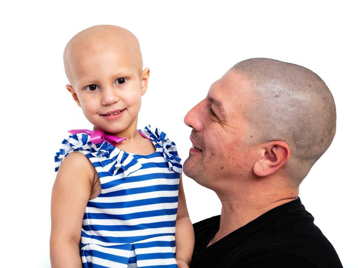 Aaron Lambert, 36, with his daughter Esme Lambert. Mr Lambert got a tattoo of his daughter's brain surgery scar so she does not feel like the 'odd one out'. (Wendy Lambert/ PA)