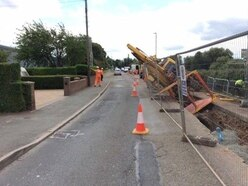 Digger collapses into trench at roadworks site