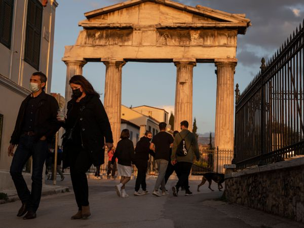 People wearing face masks walk in front of the Gate of the Ancient Roman Agora in the Plaka district of Athens