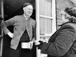 nostalgia pic. Oakengates. nostalgia pic. Ketley Bank. 'Thank you' says 86-year-old pensioner Mr Sam Bolas as Mrs Ford arrives at the front door with her containers of hot food' was the caption to this picture published in The Shropshire Star of Friday, March 5, 1965. This is a print in the Shropshire Star picture archive. It was used in a feature about how Mrs Agnes Ford, aged 53,  and her 19-year-old daughter-in-law Christine were delivering hot meals. Both were members of the Oakengates WVS meals on wheels service. WVS stood for Women's Voluntary Service, later the WRVS. 'When thick snow threatened to prevent them delivering the food on time to pensioners in Oakengates, Ketley Bank, Trench, and Hadley, they persuaded Mrs Ford's husband, Cecil, to take them round with the food containers in his smart saloon car.' Where Mr Bolas lived is not stated but the report said the Shropshire Star photographer and reporter caught up with them at Ketley Bank, so he may have lived at Ketley Bank. Library code: Oakengates nostalgia 2020. Ketley Bank nostagia 2020..
