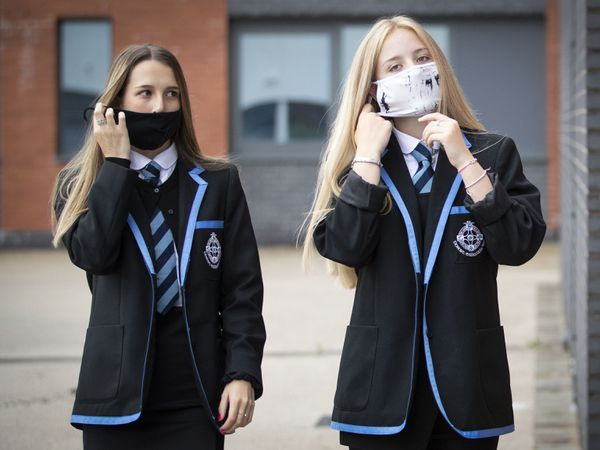 Leah McCallum (left) and Rebecca Ross, S4 students at St Columba's High School, Gourock, put on their protective face masks (Jane Barlow/PA)
