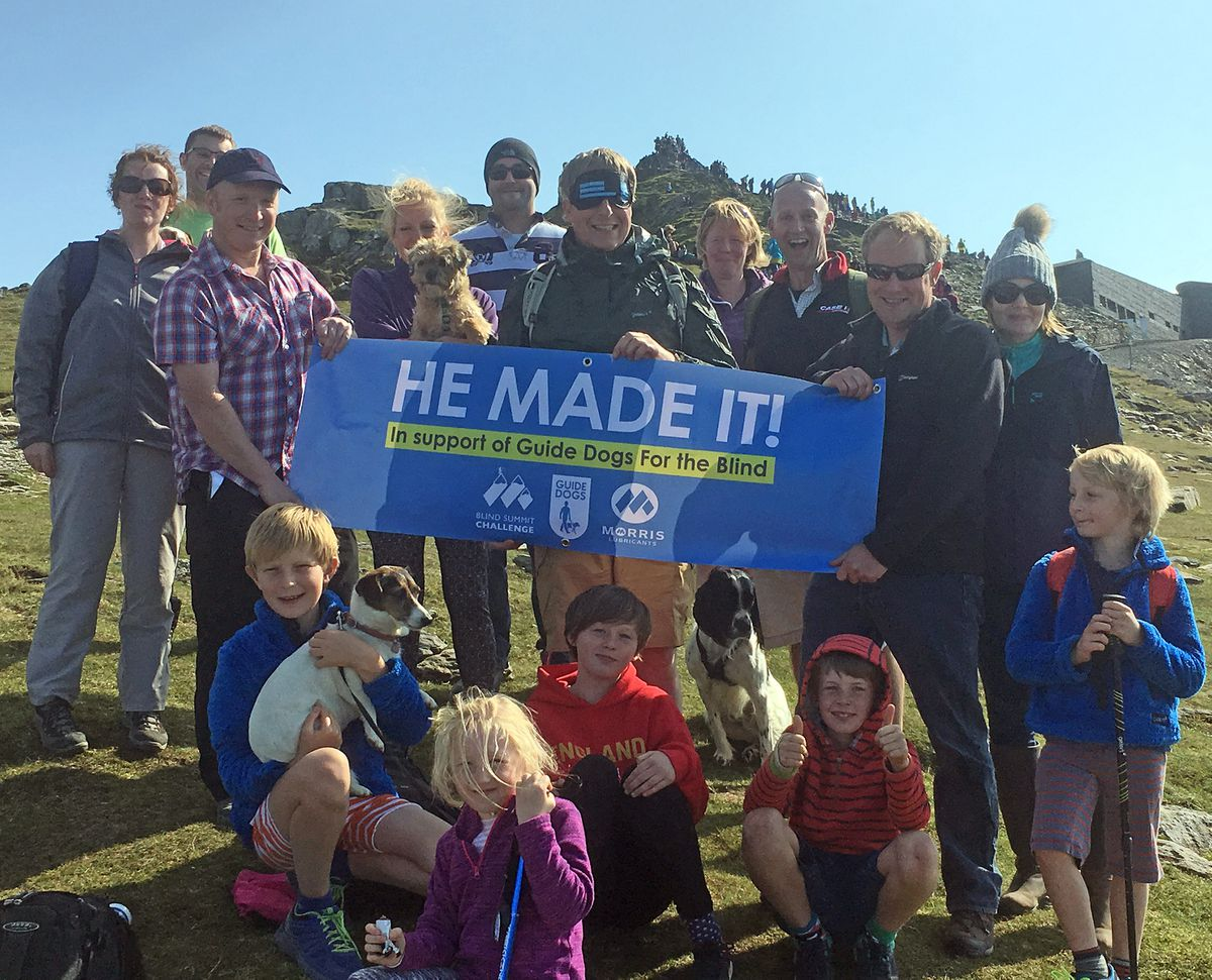 Blindfolded Andrew Goddard with his family and work colleagues at the summit of Mount Snowdon.