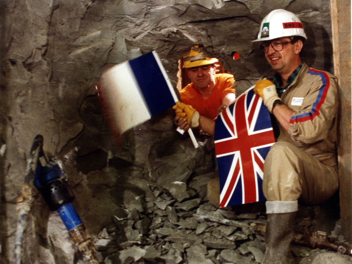 English tunneller Graham Fagg (left) exchanged flags with Frenchman Philippe Cozette as the two sides of the Channel Tunnel joined in 1990