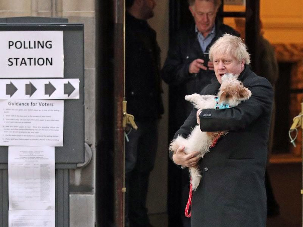 Prime Minister Boris Johnson holds his dog, Dilyn, after casting his vote in the 2019 General Election