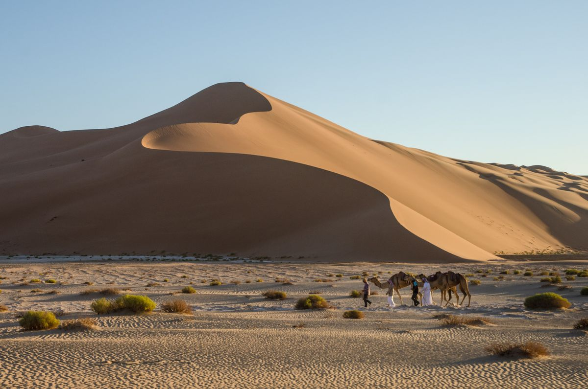 Mark Evans, front, passes the large dunes having just crossed the border between Oman and Saudi Arabia