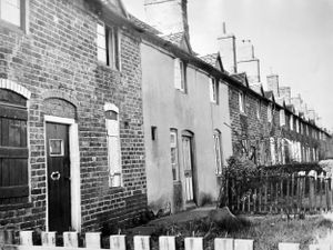 """nostalgia pic. Horsehay. The caption pasted on the back of this print in the Shropshire Star picture archive reads: 'The cottages in Old Row - mentioned in the list of buildings in Dawley New Town of 'special architectural or historic interest.' The picture was taken on April 12, 1968. The date by the caption is April 16, 1968, which was when this was published in the SS with a story that began: """"A row of 14 old cottages, where early ironworkers once lived for less than 2s. 6d. a week, has been named as of special architectural and historic interest. They are among a number of buildings and relics given protection under the 1962 Town and Country Planning Act in the Dawley New Town area. Under the Act, the buildings cannot be demolished, altered or extended unless six months' notice has been given to the local planning authority. The cottages are 3 to 17 Old Row, Horsehay, near the Horsehay Company's works. All joining each other, they were built about 130 years ago and once housed tenants of the old Coalbrookdale Company...' It said many descendants of the original occupiers still lived there, although several were now empty. The print has the Shropshire Star copyright stamp and the photographer was Bill Bishton. Library code: Horsehay nostalgia 2021. Telford nostalgia 2021.."""