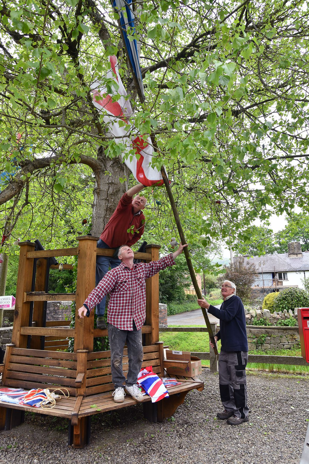 Paul Sweetland, Andy Marsden and Terry Bateman prepare the flags to keep the tradition alive in May 2021. Picture: David Bagnall