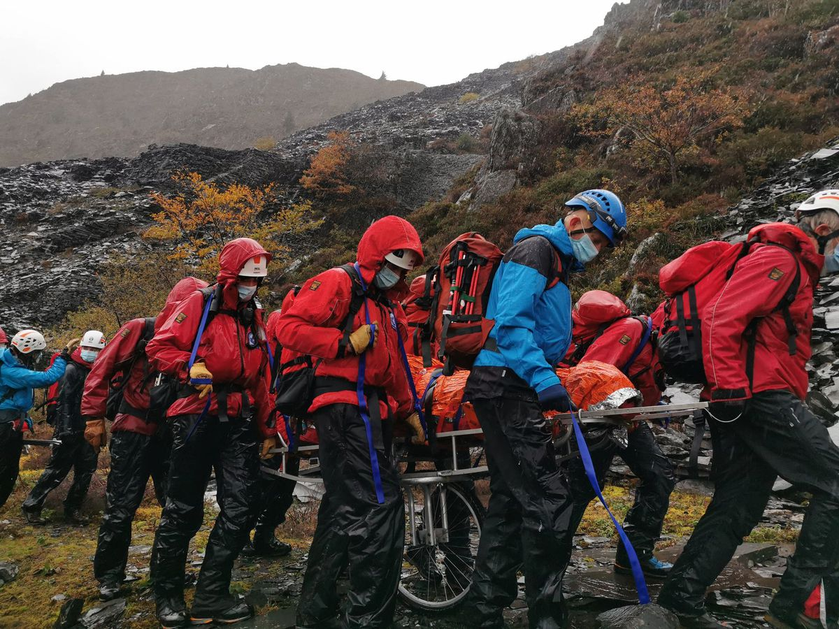 Search and rescue and ambulance crews carry the injured man to safety