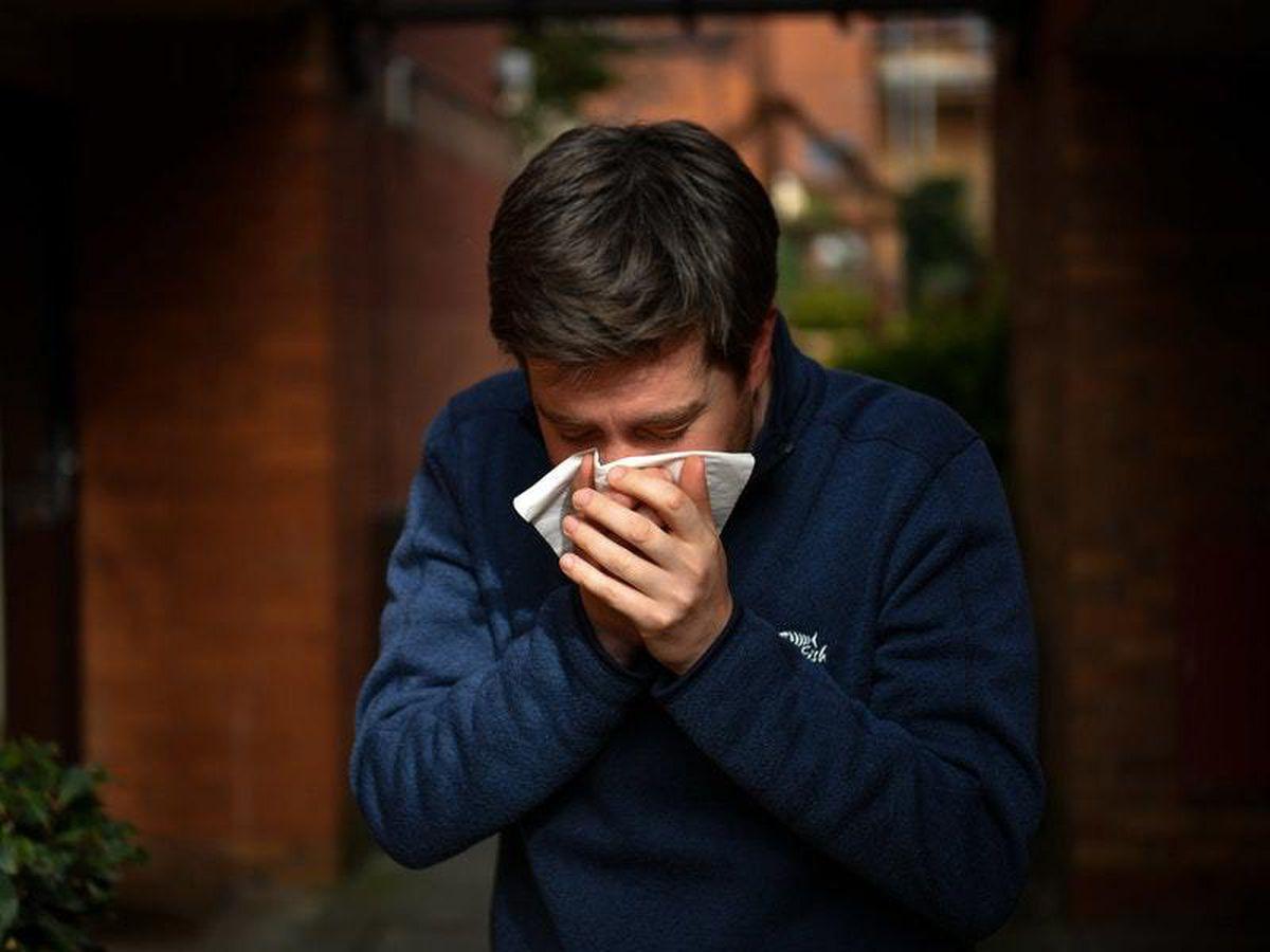 Man sneezes into hankie