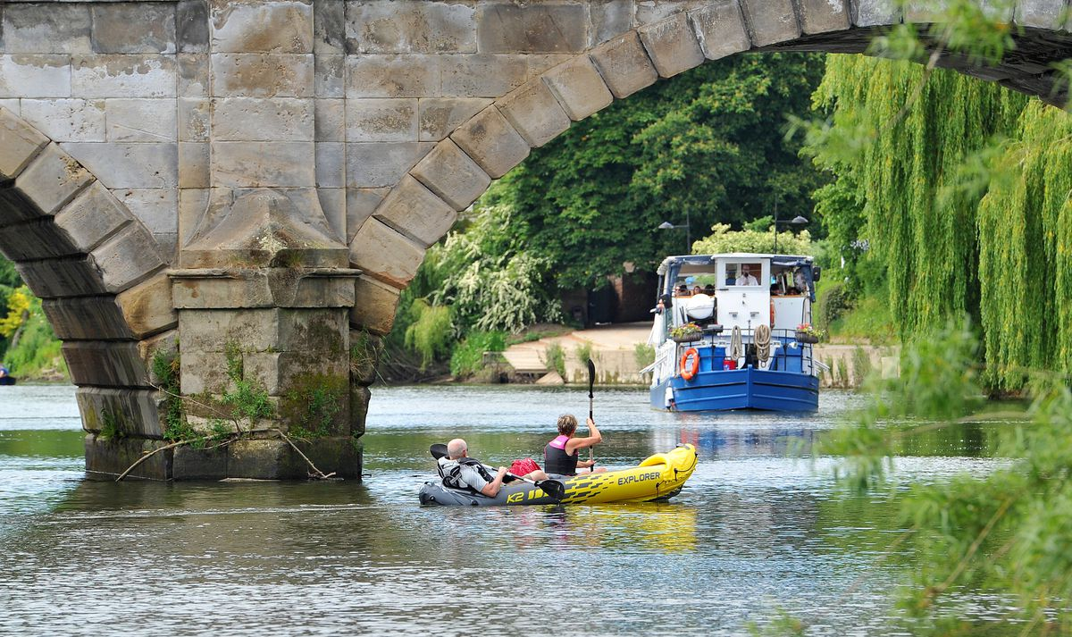 A couple enjoy a rowing boat on the river as the Sabrina boat approaches