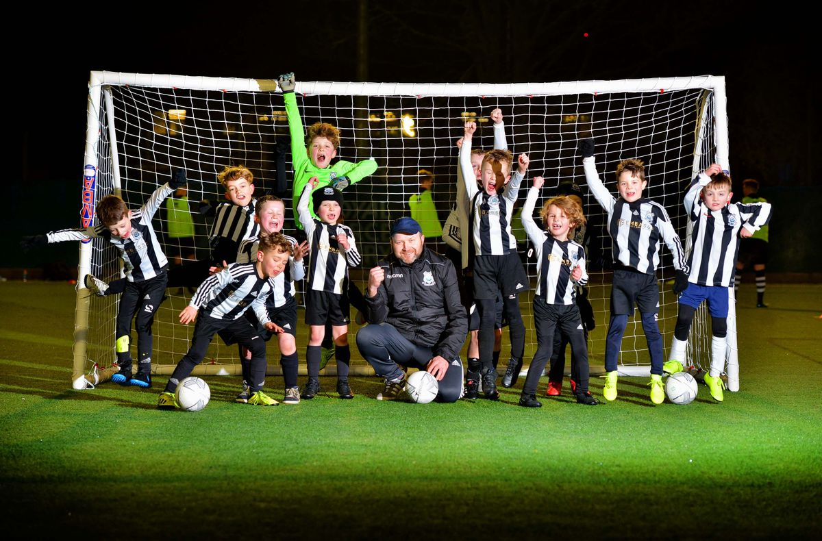 Youngsters from the club celebrate after it was gifted the 99 year lease