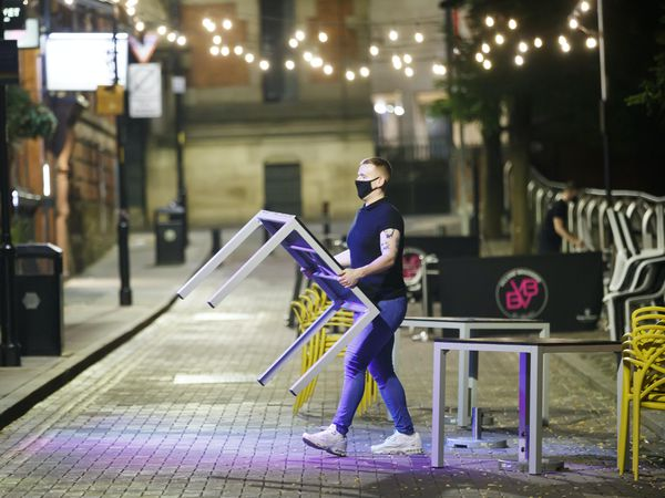 A bar worker packs tables and chairs away
