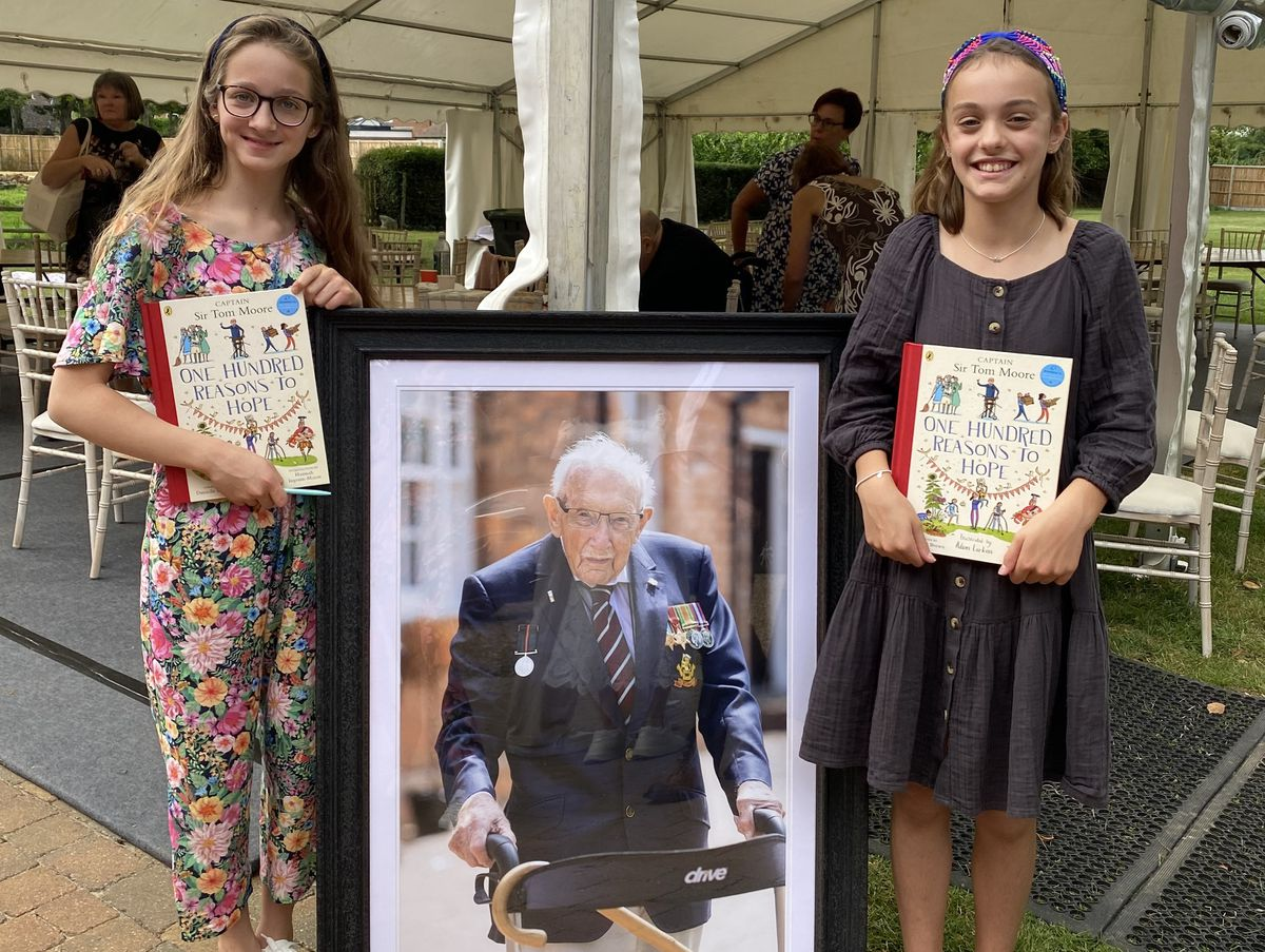Eva Spickernell (left) and friend Manon McAllister with a picture of the late Captain Tom