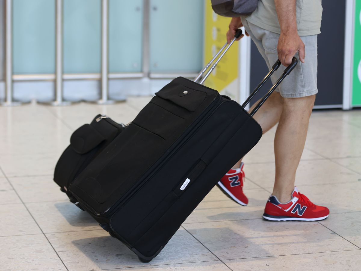 An airline passenger pulls a suitcase