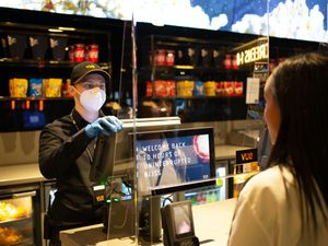 A member of staff serves a Vue cinema customer