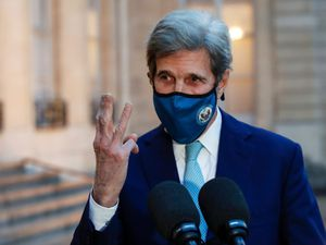 John Kerry gestures by holding up three fingers on his right hand