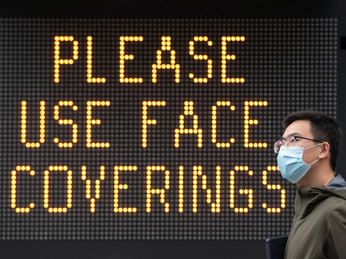 A 'Please use face coverings' notice