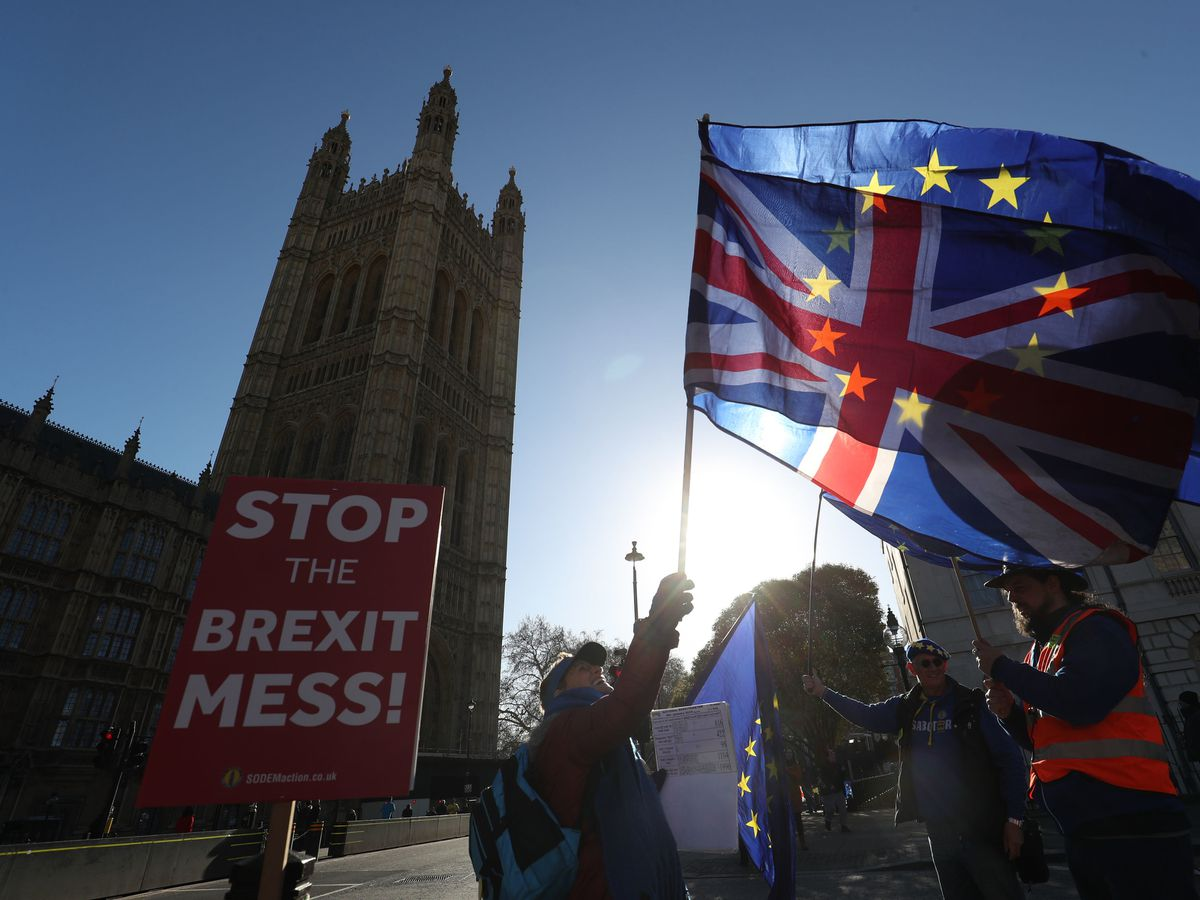 Anti-Brexit campaigners wave Union and European Union flags outside the Houses of Parliament, London, in 2019. Pic: Jonathan Brady/PA Wire