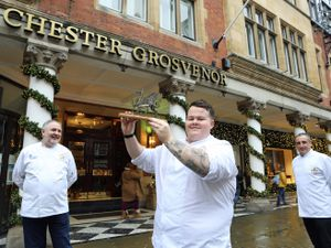 Sam Griffiths lifts aloft the National Chef of Wales trophy to celebrate his win watched by Culinary Association of Wales president Arwyn Watkins (left) and lead judge Nick Davies.
