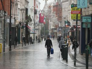 People walk along a near empty Grafton Street in Dublin city centre as Ireland remains in lockdown to help prevent the spread of coronavirus