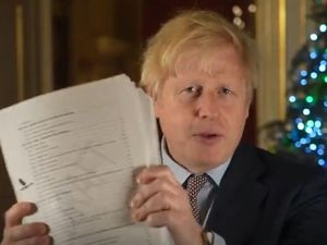 Prime Minister Boris Johnson holding up the Brexit deal during his Christmas message recorded in 10 Downing Street (@borisjohnson/PA)