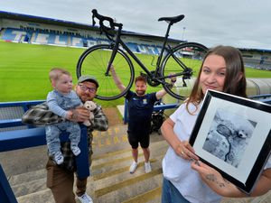 LAST COPYRIGHT SHROPSHIRE STAR STEVE LEATH 17/06/2021..Pic at AFC Telford, which will be the start point for a charity bike ride by Ian Preece. He will be cycling to Wembley, raising money for charity, inspired by his colleague at the Shropshire FA: Victoria Vespa (Pictured here holding a picture of her child she lost: Luna-Seren). Also here is Allen Vespa and there child Jude Vespa (6 months)..