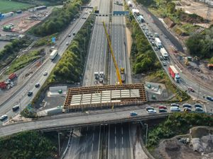 Panels are lowered onto a new bridge being built over the M6 at Junction 10. Photo: Paul Turner