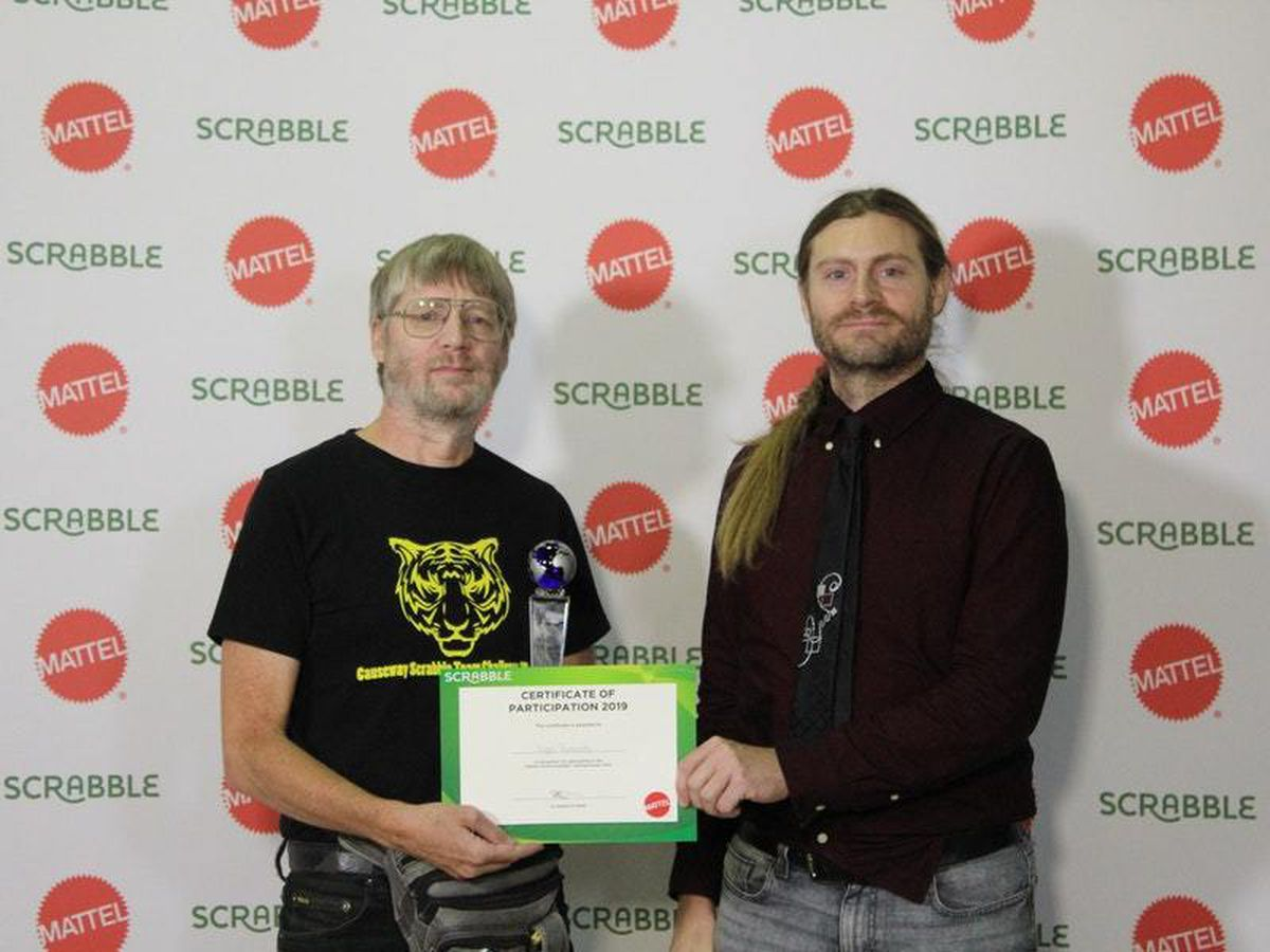 Nigel Richards (left) from New Zealand receives a certificate and trophy having won the 2019 World Scrabble Championship