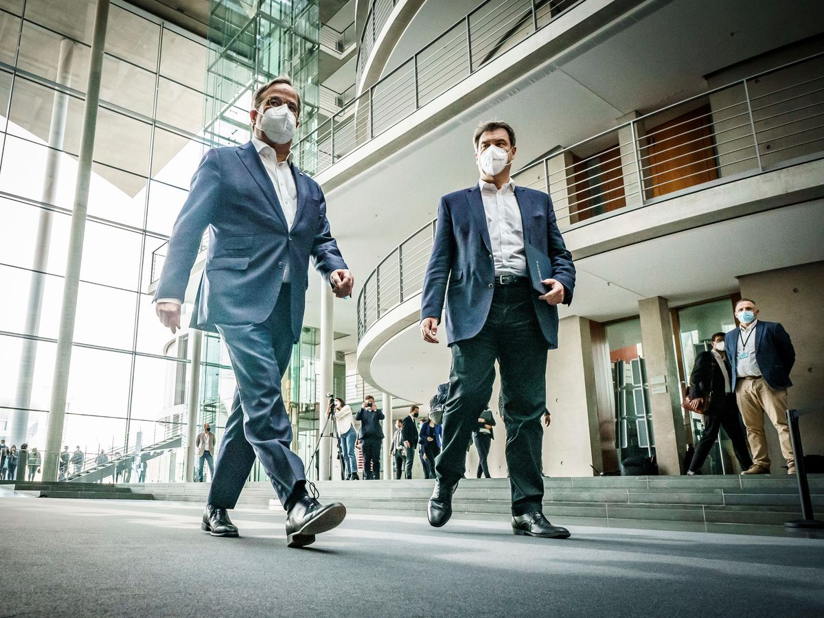 The chairman of the German Christian Democratic Party (CDU), Armin Laschet, left, and the chairman of the German Christian Social Union (CSU), Markus Soeder, right, arrive for a statement following a closed meeting (Michael Kappeler/AP)