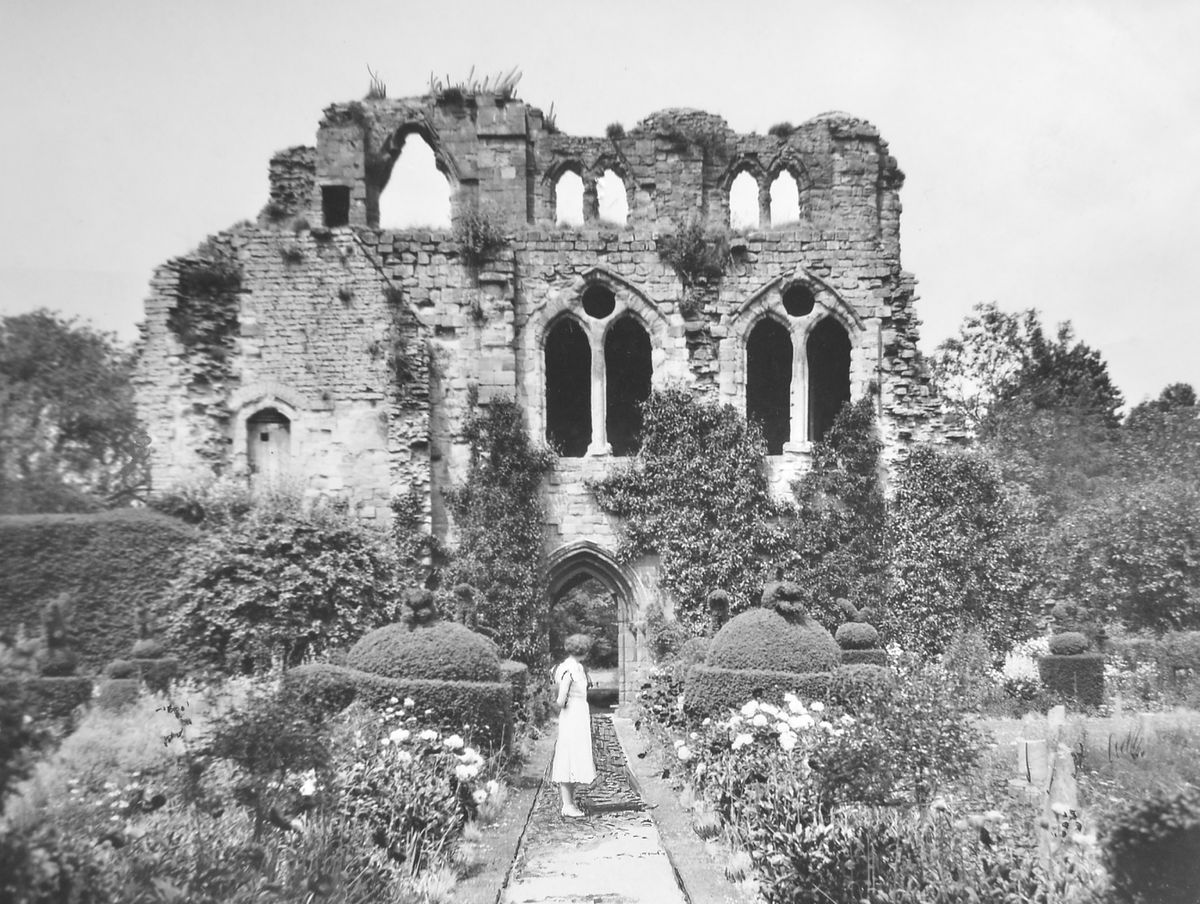 A young lady admires the blooms amid the picturesque ruins of Wenlock Abbey at Much Wenlock. If that young lady is still with us, she must be pushing 100 now, as this photo dates from April 1938