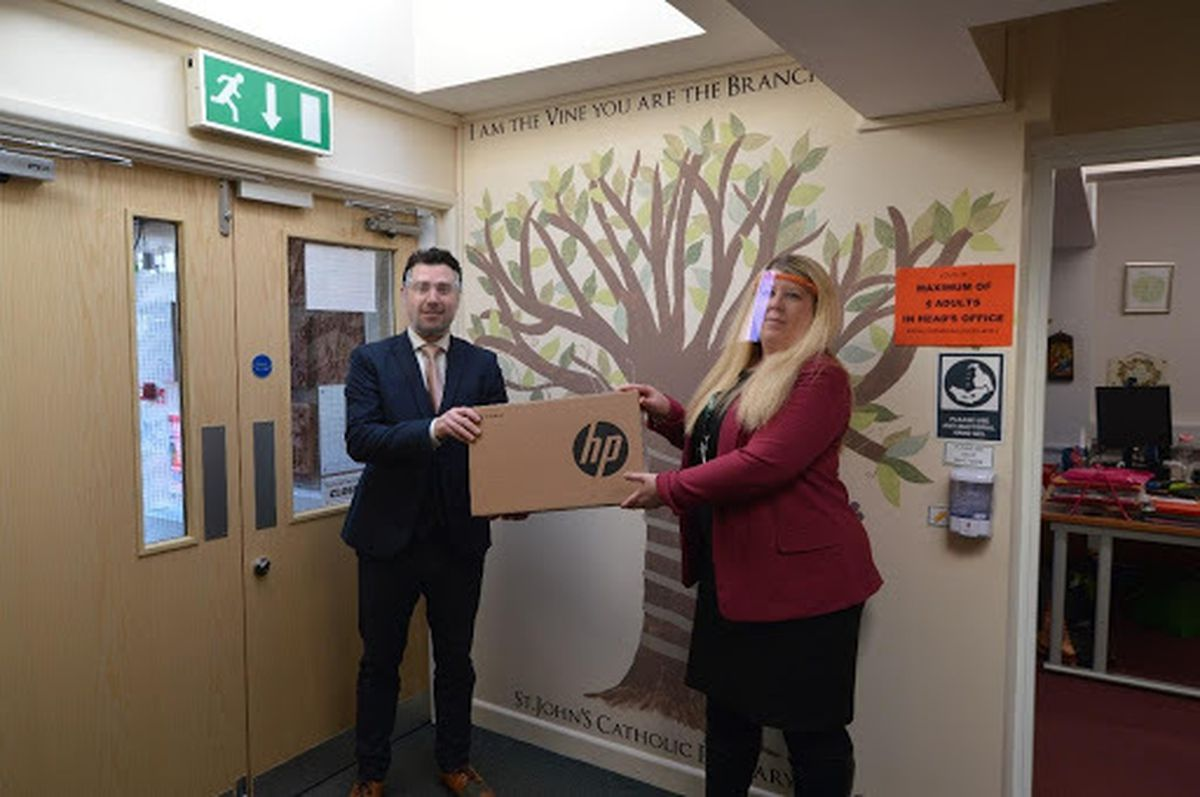 Andrew Ainge, branch principal of Nock Deighton, Bridgnorth delivering the laptop to St John's Catholic Primary School headteacher Jessica Buzzing