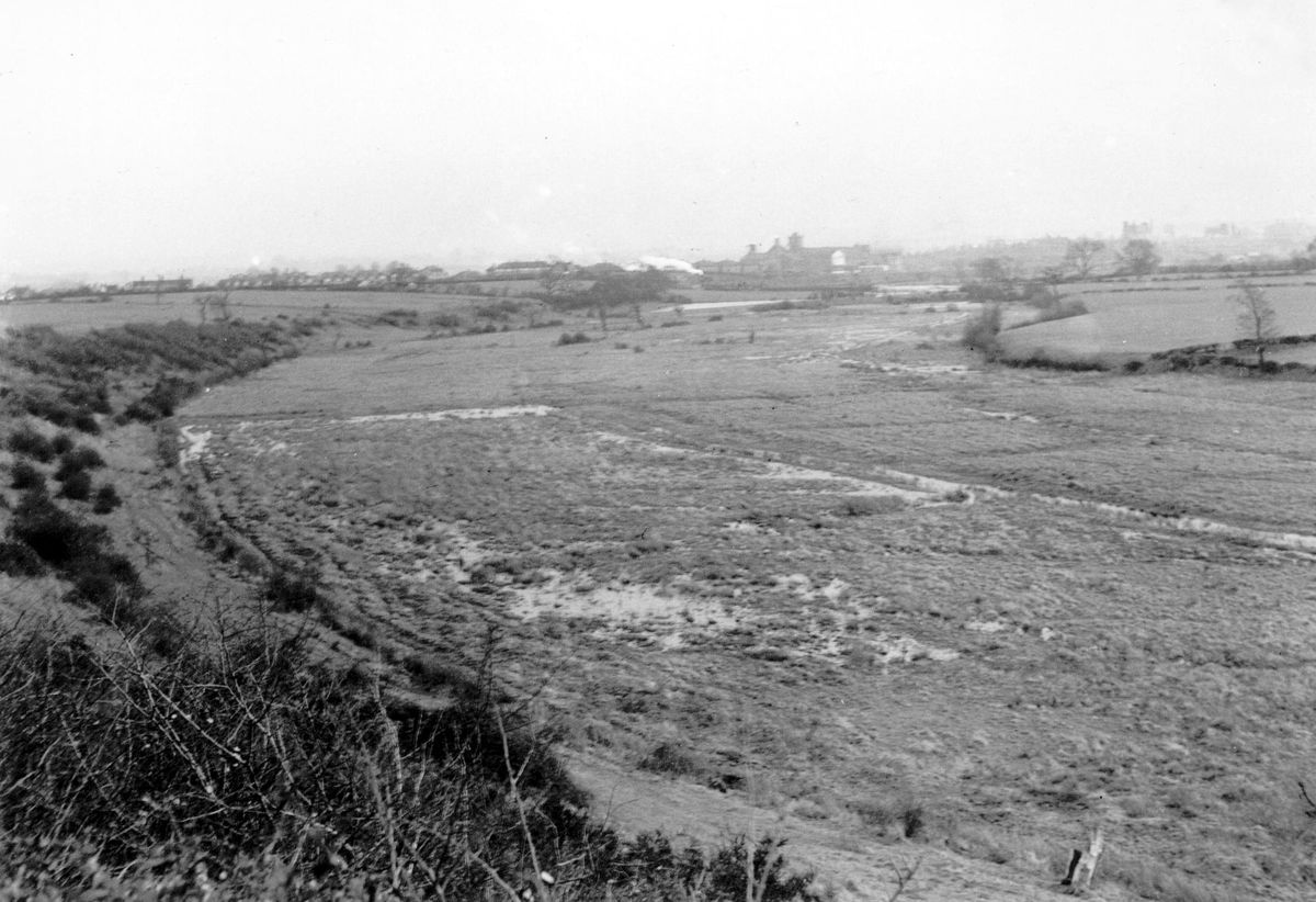 """This picture taken by the late Stan Turner of Shrewsbury shows the old river bed viewed from Cross Hill, Ellesmere Road, Shrewsbury. Mr Turner explained: """"I took this photo in 1958 as the rising flood waters were starting to back up in the old bed. The view is looking east towards the Shrewsbury-Crewe railway line – note the steam train – and the distant Maltings. The field, top left, is now part of the Mount Pleasant Estate, and Hubert Way now runs along the right side. The Bagley Brook rises in this section of the old bed which is now a local nature reserve."""""""