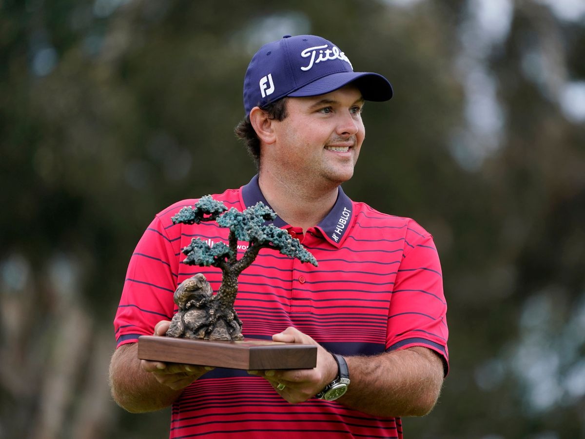 Patrick Reed stands on the South Course while holding his trophy