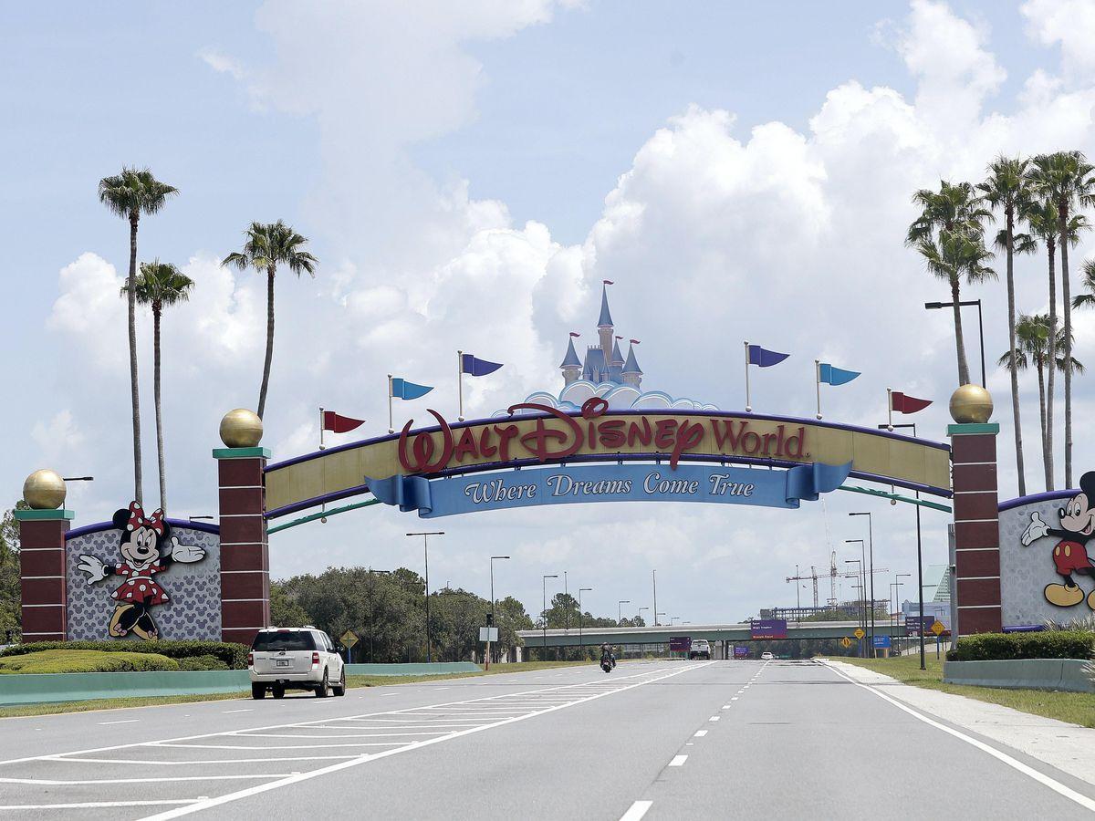Cars drive under a sign greeting visitors near the entrance to Walt Disney World, in Lake Buena Vista, Florida (Jon Raoux/AP)