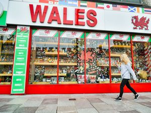 A woman wears a face covering as she walks past a shop in Cardiff