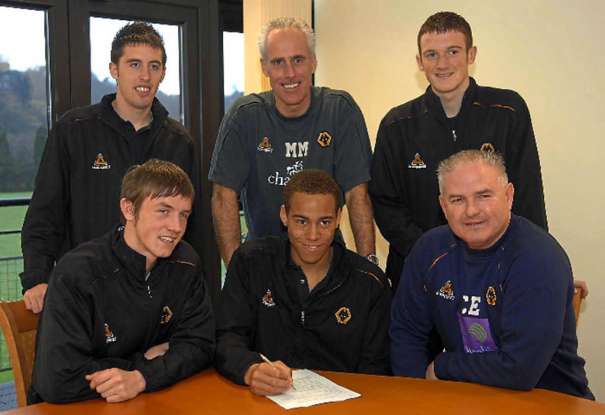 Lee Collins (back right) celebrates signing a Wolves contract, along with Mark Salmon (back left), Liam Hughes (front left) and Elliott Bennett (front centre) – with Wolves manager Mick McCarthy and academy director Chris Evans