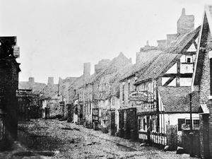 """Is this the oldest picture of Market Drayton? It is Cheshire Street, and on the right is the Royal Oak Inn, and on the left is the Drovers Arms, where the licensee is """"Roden."""" If this really is the oldest picture it may be from around the 1850s and although there doesn't appear to be anybody about, that is deceptive as they may not have stood still long enough to be captured by the long exposure times needed by the photography of the day."""