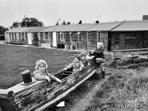 """nostalgia pic. Bicton. Children play outside Bicton village hall in October 1974. This is a print in the Shropshire Star picture archive and was published on Monday, October 14, 1974, and used with a story saying Bicton had far-reaching plans for the development of its village hall, but said the scheme had run into a stumbling block because Salop County Council considered the plans too ambitious and had not approved two applications for grant aid. The council was unhappy with the design, which was for a smaller hall. 'The present hall, which is in almost constant use, is an ex-wartime building which was erected in 1951 in a field bought with £600 of the £1,000 villagers raised between 1943 and 1950."""" The story said two applications for a new hall had been submitted. The print has the Shropshire Star copyright stamp and the photographer was Dave Bagnall. Library code: Bicton nostalgia 2020.."""