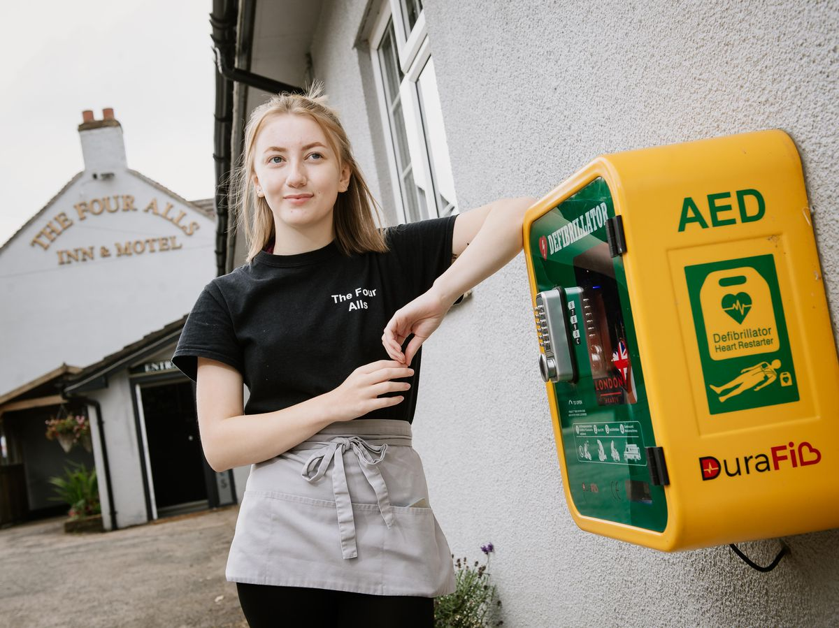 Staff member Amelia Fleet with the defibrillator at The Four Alls Inn
