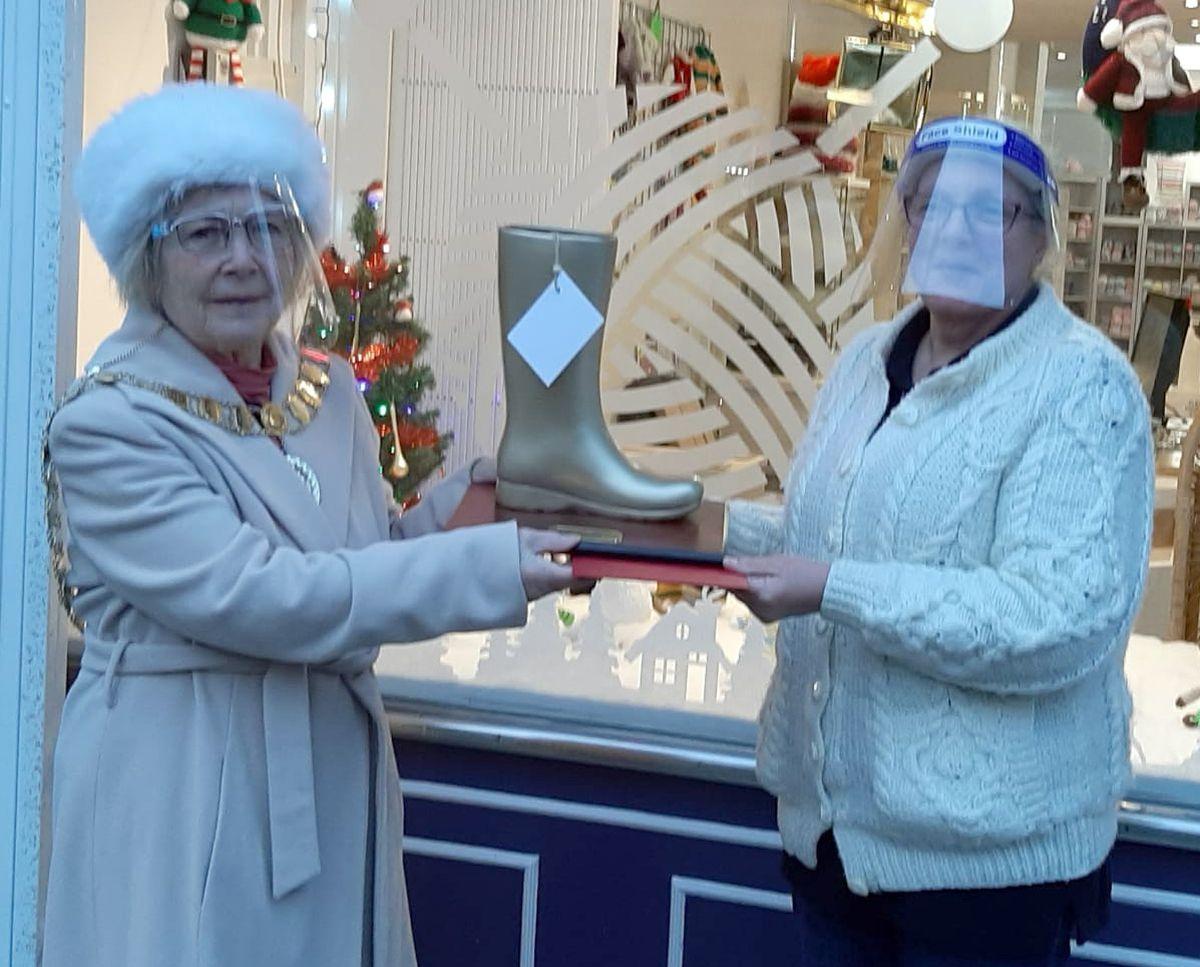 Wellington Mayor Pat Fairclough, left, presents a golden wellington boot award to Donna Thomas of Wool Magic.