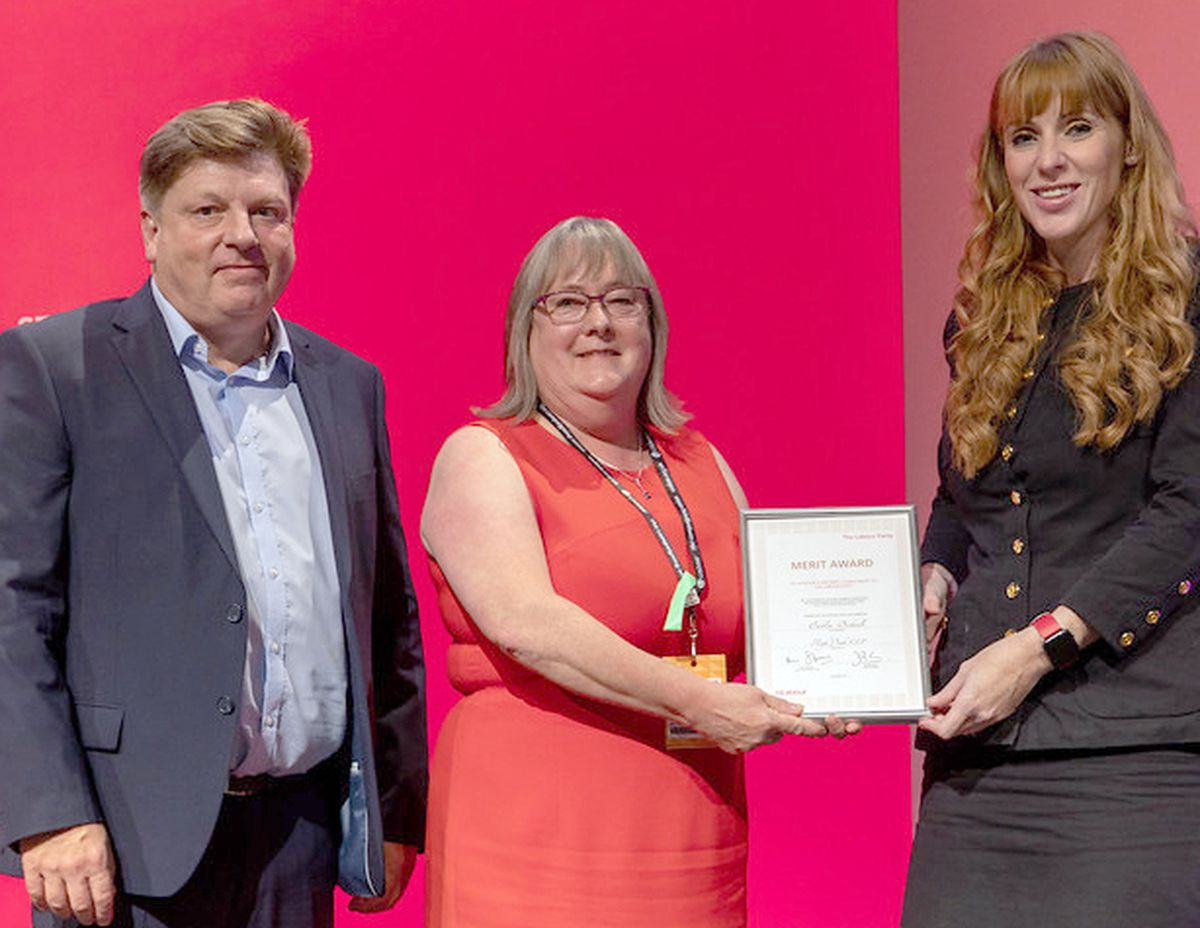 Caitlin, centre, receives the award from Angela Rayner and David Evans