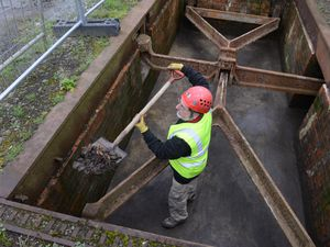 Andrew Wood cleaning up leaves from the bottom of the weighbridge which has the tops plates removed